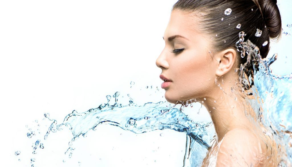 Beautiful Model Woman with splashes of water in her hands. Beaut